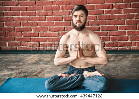 Handsome young man with dark hair and beard wearing trousers doing yoga lotus position and sitting on blue matt at wall background, copy space, portrait, namaste mudra.