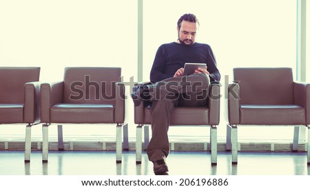 Handsome young man with dreadlocks using his digital tablet pc at an airport lounge, modern waiting room, with backlight. - stock photo