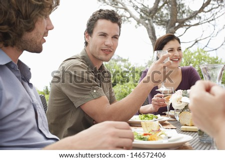 Handsome young man with friends enjoying dinner party outdoors - stock photo