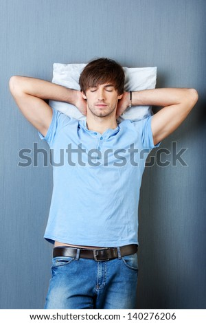 Handsome young man with hands behind head sleeping on blue wall - stock photo
