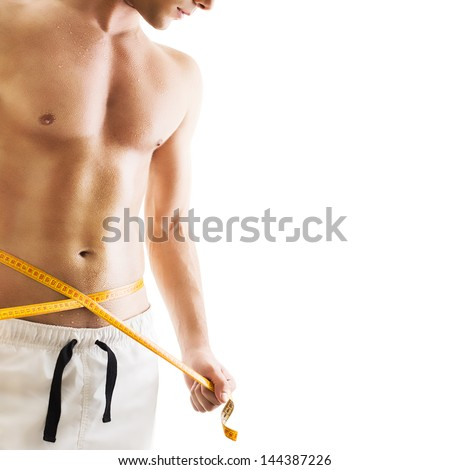 Handsome young man with measuring tape - stock photo