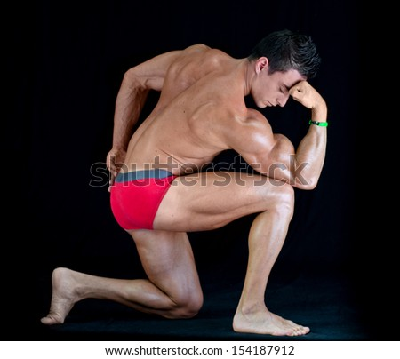 Handsome young man with muscular body in classic pose on his knee, isolated on black - stock photo