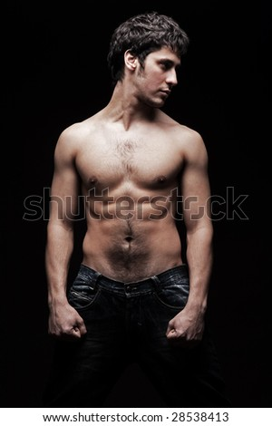 handsome young man with naked torso posing against dark background - stock photo