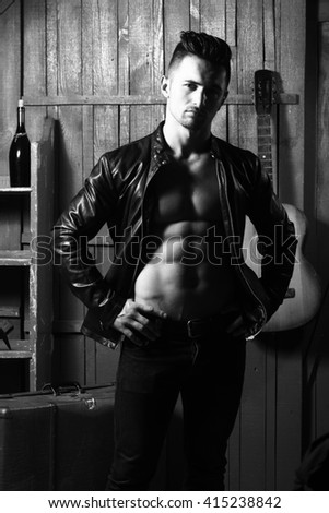 Handsome young man with sexy muscular bare torso in leather jacket standing with acoustic guitar and wine bottle on wooden background, black and white