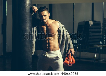 Handsome young man with sexy muscular body bare torso and chest near punching bag in boxing gloves - stock photo