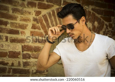 Handsome young man with sunglasses and white t-shirt, outdoors next to brick wall - stock photo