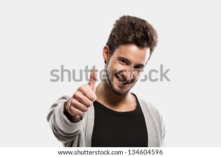 Handsome young man with thumbs up, over a gray background - stock photo