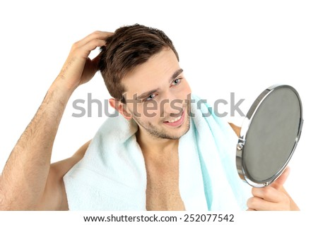 Handsome young man with towel holding mirror isolated on white - stock photo