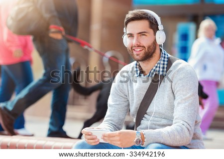 Handsome young man with white headphones outside in the town - stock photo