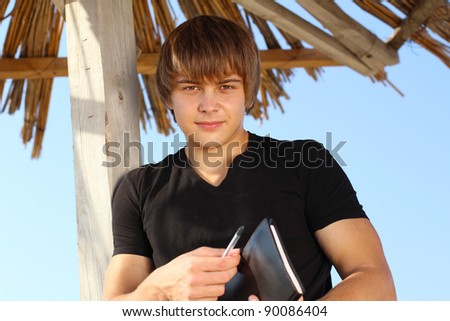 Handsome young man with writing pad, outdoors - stock photo