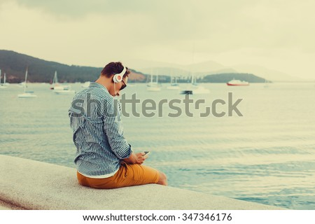 Handsome young man working abroad,relaxing  and  listen music on his earphones,young guy with beard,casual street style cloth,grey shirt,music in headphones on a smartphone,freedom concept man - stock photo