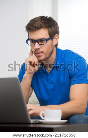 handsome young man working on computer laptop at home. serious guy looking at screen and holding chin - stock photo