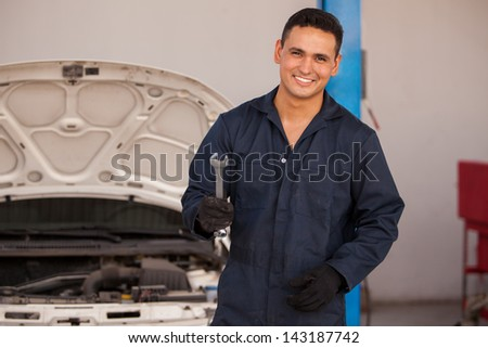 Handsome young mechanic wearing an overall and smiling while holding a wrench - stock photo