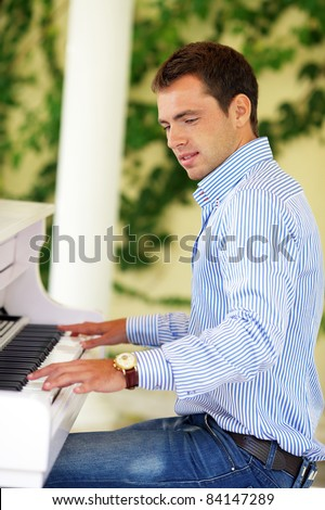 Handsome young men playing white luxury piano in the garden - stock photo