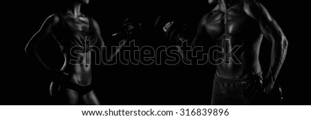 handsome young muscular couple doing exercises with dumbbells - stock photo