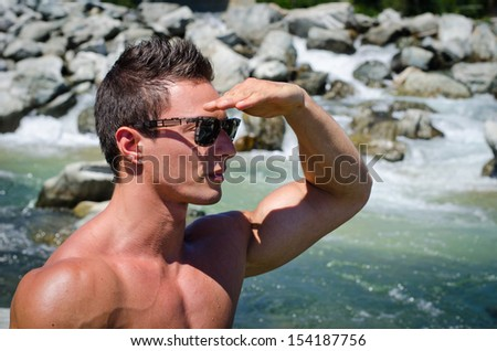 Handsome young muscular man shielding eyes with hand to look far, to a side
