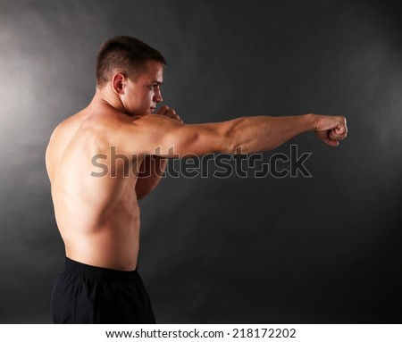 Handsome young muscular sportsman boxing on dark background