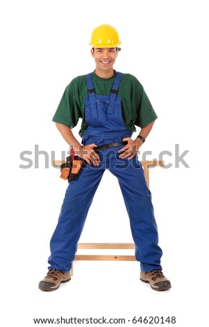 Handsome young Nepalese carpenter wearing a blue overall and with the hands on the tool-belt. Studio shot. White background. - stock photo