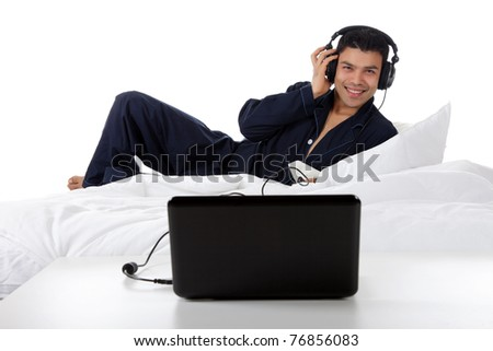 Handsome young nepalese man in pajamas with headphones and laptop, relaxing in bed and listening music from the internet. Focus on laptop. Studio shot. White background. - stock photo