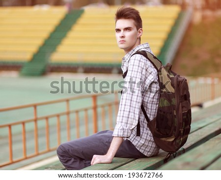 Handsome young pensive man with backpack, modern hipster sitting on a bench - stock photo