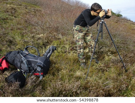 handsome young photographer taking landscape photos outdoors - stock photo