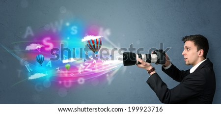 Handsome young photographer with camera and abstract imaginary - stock photo