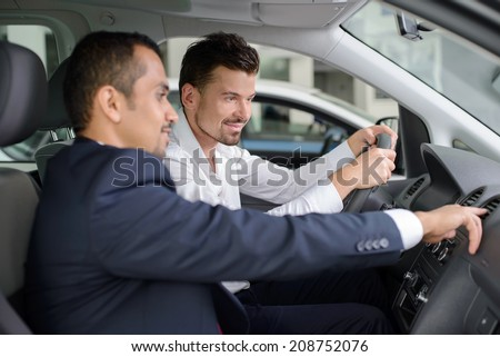 Handsome young salesman showing all the car features to the customer