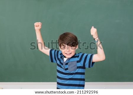 Handsome young schoolboy celebrating in the classroom cheering and punching his fists in the air - stock photo