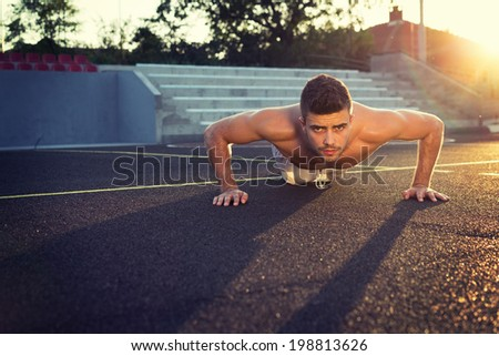 Handsome young shirtless Caucasian fitness man doing push-ups outdoors on sunny summer day. Back lit horizontal image. - stock photo