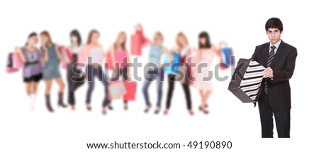 Handsome young shopping man with girls holding bags on background