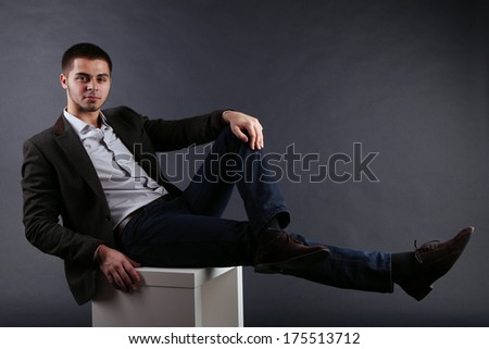 Handsome young sitting on cube on dark background