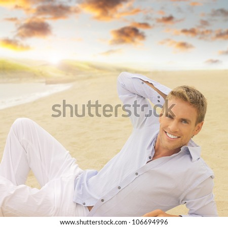 Handsome young smiling man laying down outdoors with beautiful sky - stock photo