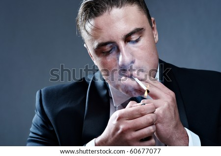 Handsome young smoker igniting cigarette - stock photo