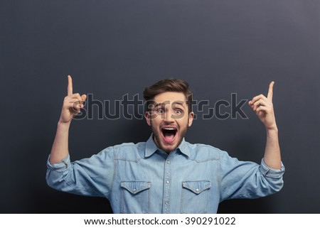 Handsome young student in jeans shirt is pointing up, looking at camera, shouting and smiling, standing against blackboard - stock photo