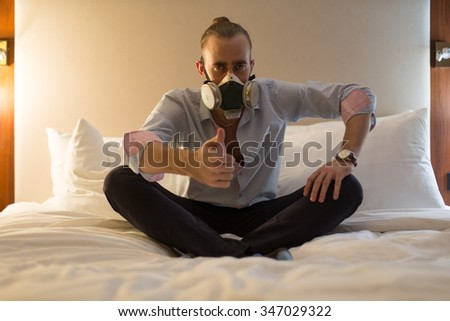 Handsome young stylish caucasian man in respirator sitting on the bed in the bedroom