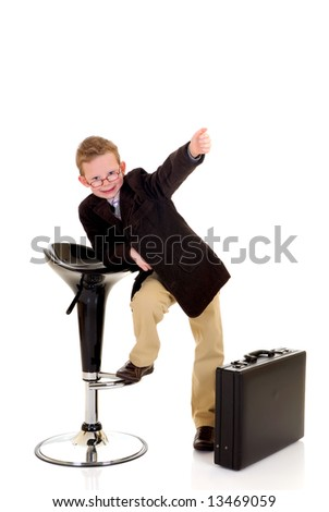 Handsome young successful child next to briefcase and bar stool  making okay gesture, white background,  studio shot.