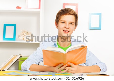 Handsome young teen boy reading book doing homework at home - stock photo