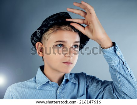 Handsome young teenage boy posing in studio with fashionable hat - stock photo