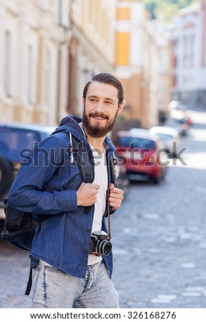 Handsome young tourist is walking across city with backpack. He is smiling and looking aside happily. The man is holding camera - stock photo