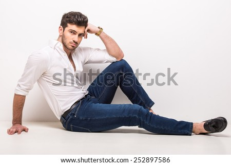 Handsome, young, trendy man is sitting on the floor in studio on gray background. - stock photo