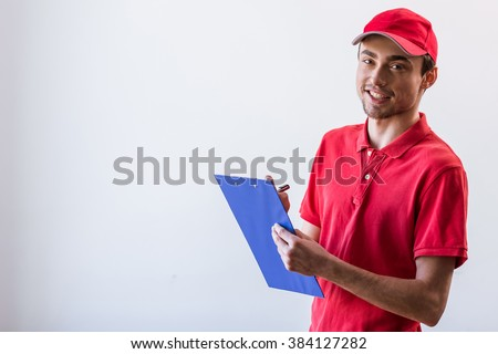 Handsome young worker in red t-shirt and cap smiling, holding a folder and making notes, on white background - stock photo