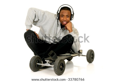 Handsome youngster, black African American teenager with mountain-board and headset, hip hop urban culture.  Studio white background - stock photo