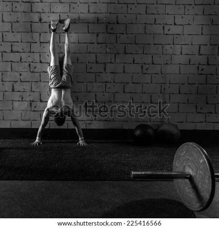 Handstand push-up man workout at gym pus ups - stock photo