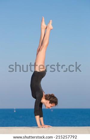 Handstand. Young gymnast on seashore - stock photo