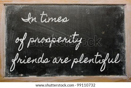 handwriting blackboard writings - In times of prosperity friends are plentiful - stock photo