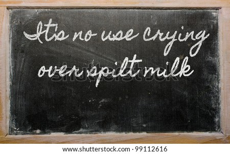 handwriting blackboard writings - It's no use crying over spilt milk - stock photo