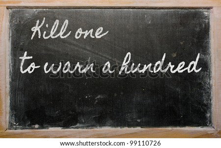 handwriting blackboard writings - Kill one to warn a hundred - stock photo