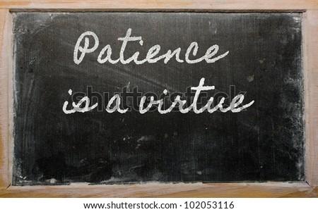 handwriting blackboard writings - Patience is a virtue - stock photo