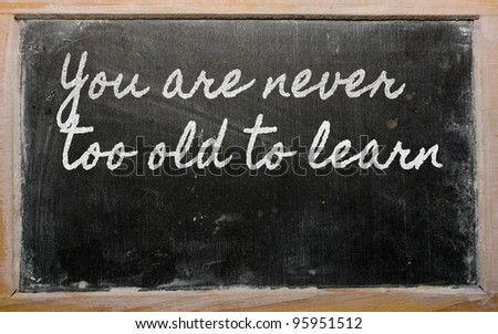 handwriting blackboard writings - You are never too old to learn - stock photo