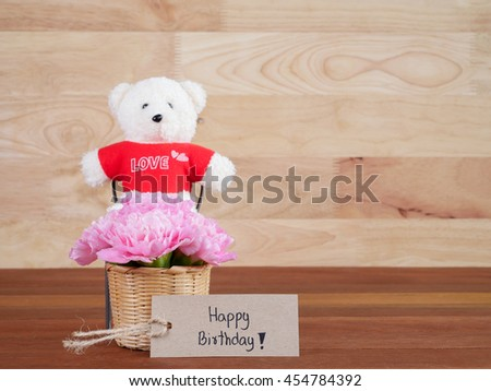 Handwriting Happy Birthday on brown label and bouquet of sweet pink Carnation flower in basket and teddy bear on wood background - stock photo